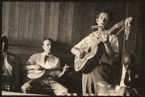 Pete Seeger (banjo) sentado e Woody Guthrie (gaita e violão) em pé
