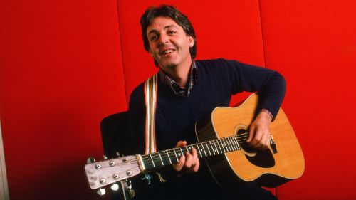 Portrait of British musician Paul McCartney as he plays acoustic guitar against a red background, October 7, 1984 . (Photo by Robert R. McElroy/Getty Images)
