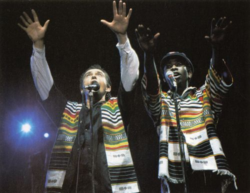 This photograph shows Peter Gabriel and Youssou NDour performing on stage. The Human Rights Concerts featured musicians such as Sting, The Police, Peter Gabriel, U2, Bruce Springsteen, Radiohead, Joan Baez, and many others. Over 1,250,000 people around the world attended these concerts in person, and millions more experienced them on television and radio. This series of 28 rock concerts presented worldwide between1986-1998 raised funds for and awareness of Amnesty International worldwide. This photograph was taken during one of the Human Rights Now tour concerts which was a twenty-concert world tour held over a six-week period in September–October 1988. The tour commemorated the 40th anniversary of the Universal Declaration of Human Rights. The tour starred Bruce Springsteen & the E Street Band, Sting and Peter Gabriel with Tracy Chapman and Youssou N'Dour. Guest musicians who made appearances during the tour included Bono, Joan Baez, k.d. lang and Pat Metheney. The twenty concerts took place in fifteen different countries on five continents (Europe, Asia, Africa, North America and South America). In each country the concert also featured performances by popular local musicians.